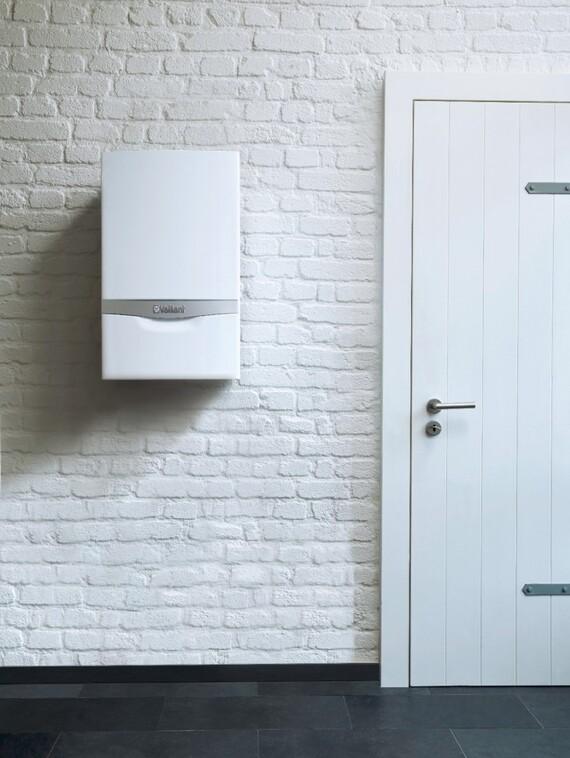 Kocioł gazowy ecoTEC plus VU powieszony na białej ścianie obok drzwi